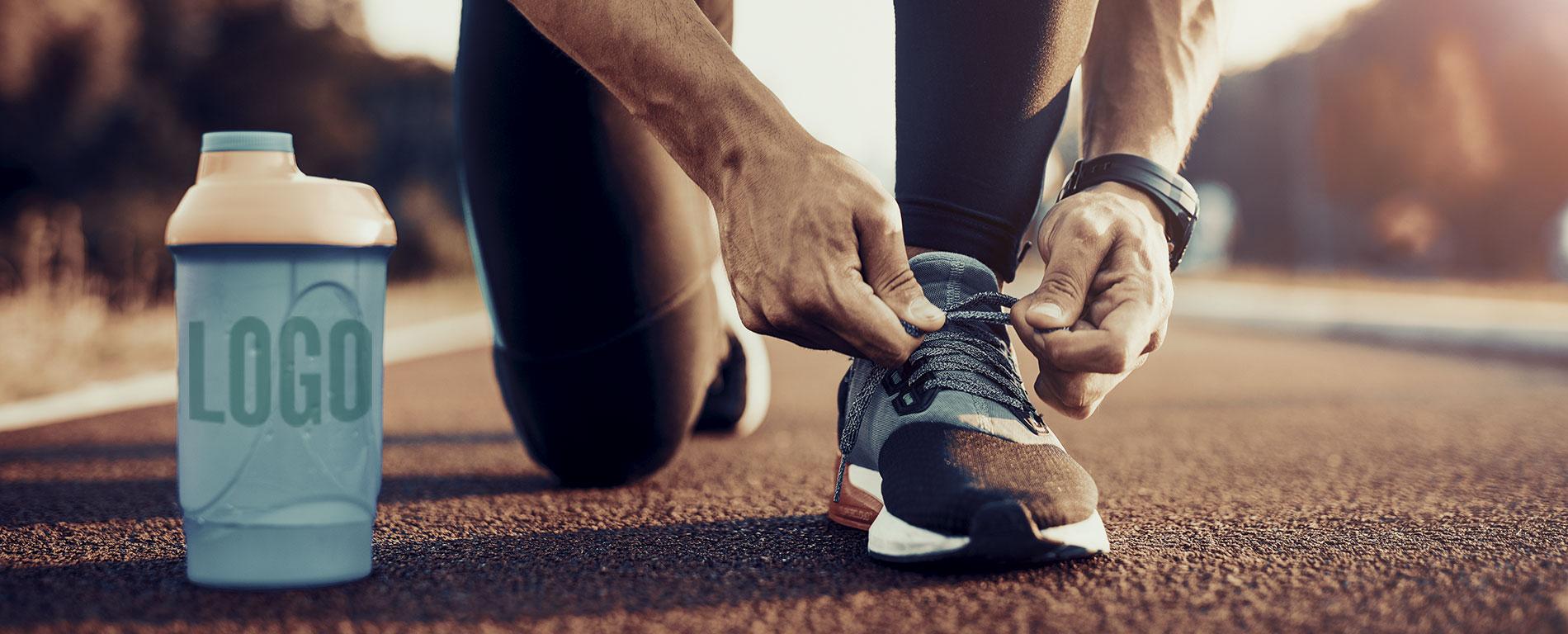 D-max Print – Produktplacering – Man knyter skorna bredvid en flaska med logotype